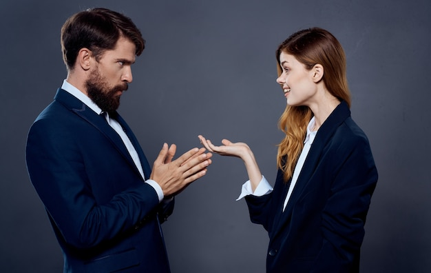 Business man and woman in suit gesturing with hands on gray space cropped view