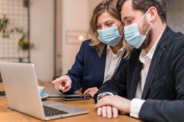 Uomo e donna di affari che parlano di un nuovo progetto mentre indossano maschere mediche
