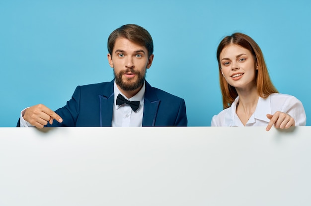 Business man and woman with white mockup poster advertising sign copyspace studio