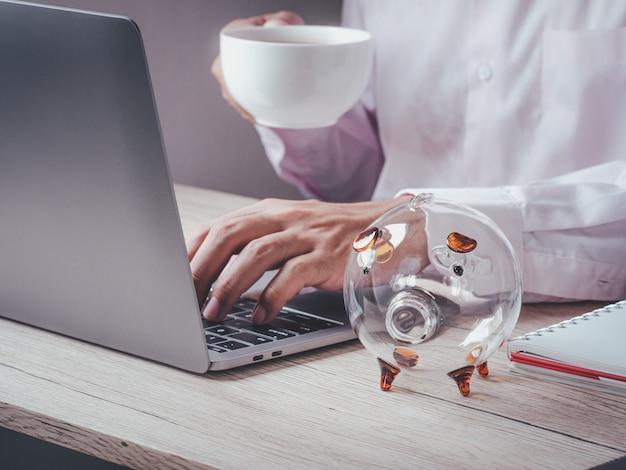 일하는 비즈니스 사람과 사무실에서 나무 테이블에 돼지 저금통. 미래 계획 및 퇴직 기금, 비즈니스 또는 금융 저축 및 투자 비용을위한 저축