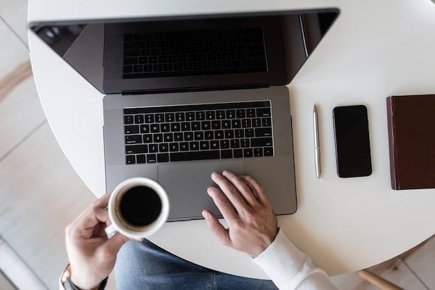 노트북에서 일하고 카페의 테이블에 앉아있는 동안 커피를 마시는 비즈니스 남자