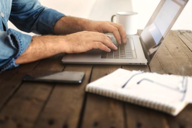 Деловой человек, работающий дома с ноутбуком. рука человека, набрав на компьютере. концепция удаленной работы или образования