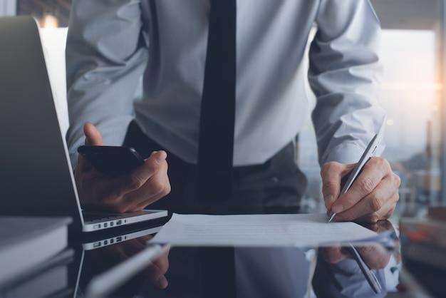 현대 사무실에서 일하고 비즈니스 문서에 서명하는 비지니스 맨
