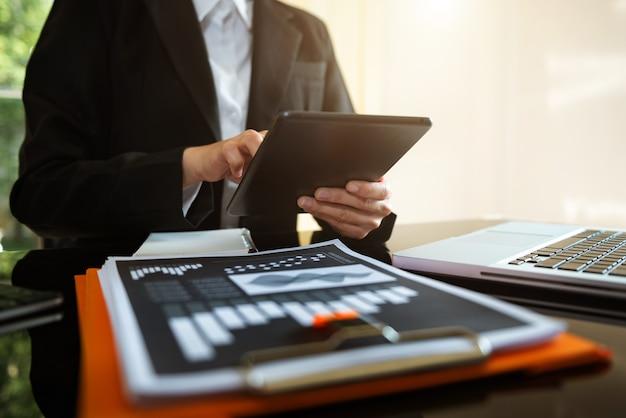 彼の机の上のラップトップとドキュメントを持ってオフィスで働いているビジネスマンは、新しいスタートアッププロジェクトを開始します。財務タスク。
