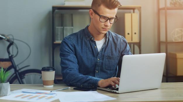 ノートパソコンとオフィスで働いていると電話を使用してビジネスの男性