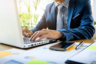 Business man working at office with laptop, tablet and graph data documents on his desk