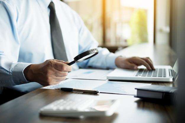Деловой человек, работающих в офисе с ноутбуком, планшета и графика данных документов на своем столе