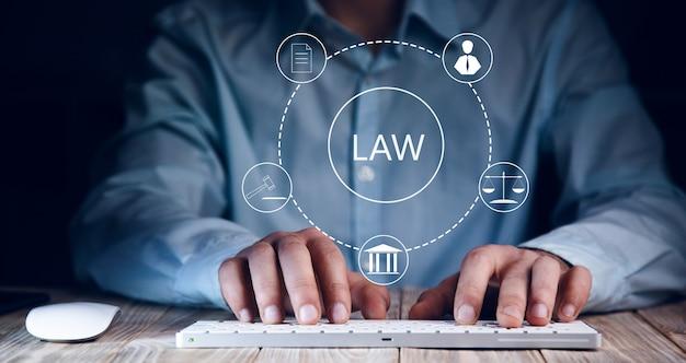 Lawアイコンでコンピューターを操作するビジネスマン