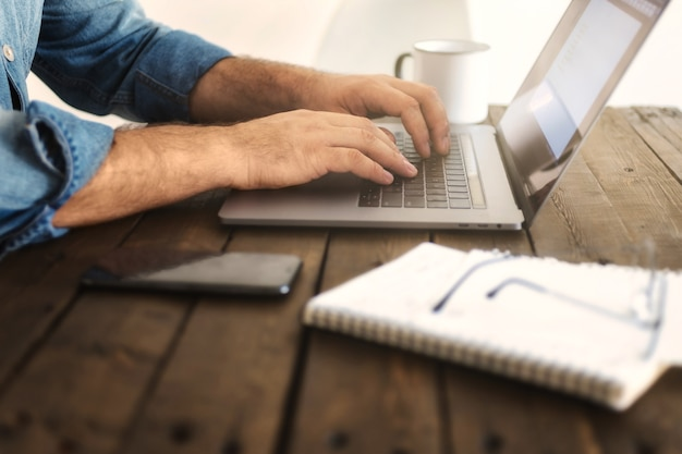 Business man working at home with laptop. man hand typing on a computer. remote work or education concept