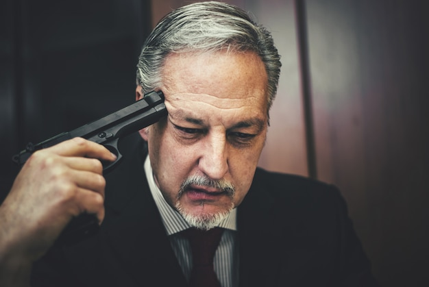 Business man working on laptop with someone pointing a gun at his head