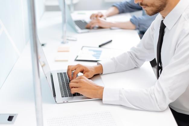 Деловой человек, работающий на ноутбуке в офисе