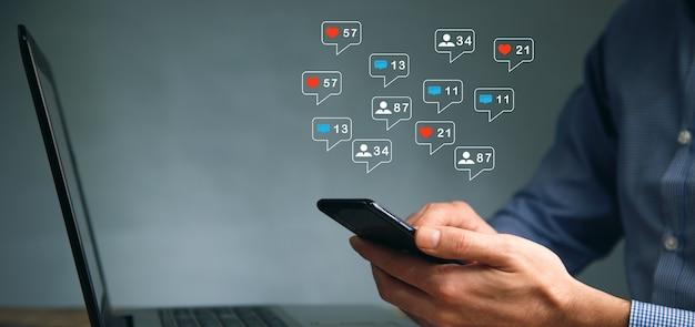 소셜 네트워크에서 메시지와 함께 컴퓨터와 전화에서 작업하는 비지니스 맨