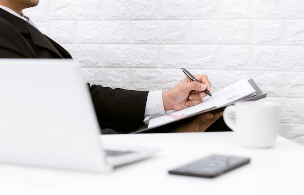 テーブルの上のコンピューターのコーヒーと電話を探しているドキュメントに取り組んでいるビジネスマン