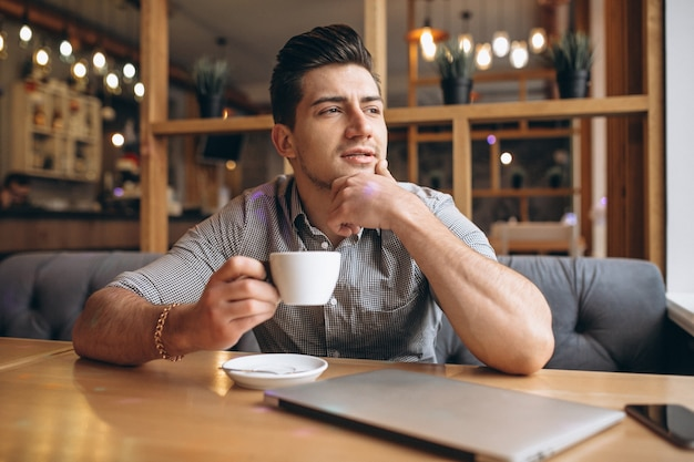 Деловой человек, работающий на ноутбуке в кафе
