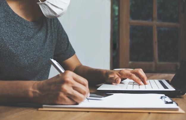 自宅の木製のテーブルでノートパソコンを操作するビジネスの男性。オンラインビジネスコンセプト。