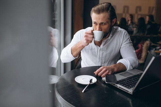 Business man working with laptop and drinking coffee in a cafe