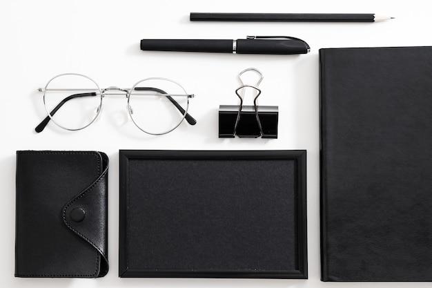 Деловой человек на рабочем месте. очки, черные канцелярские товары и офисные принадлежности, расположенные на белом фоне