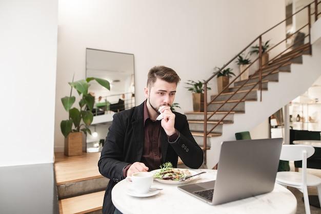 ビジネスの男性はラップトップのために働いて、レストランでサラダとコーヒーで朝食を持っています