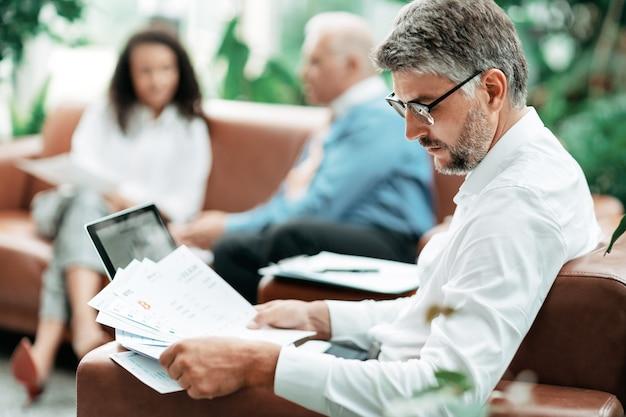 ビジネスマンは、財務書類のクローズアップで動作します
