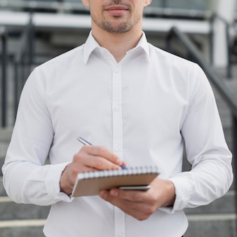 Business man writing in notepad
