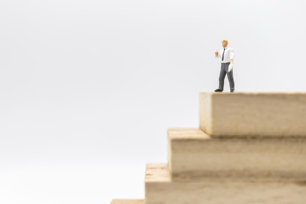 Business, management and planning concept. businessman miniature figure standing and working on top of stack of wooden bloack toy
