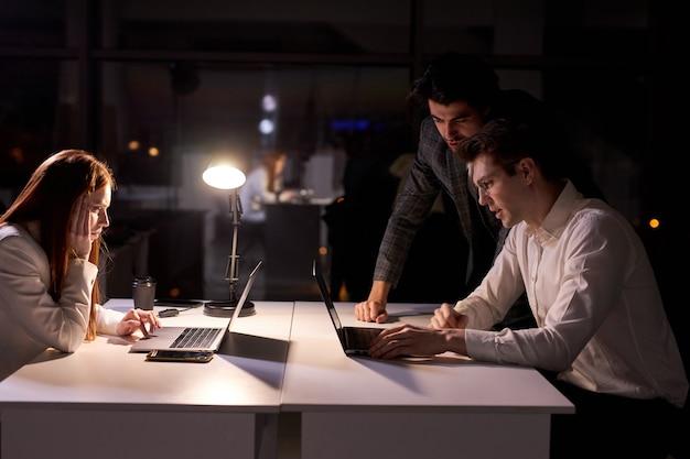 Бизнес-менеджер и сотрудники вместе работают над проектом, используя ноутбук в офисе поздно ночью, проводят мозговой штурм, много думают, решают задачи и вопросы. вид сбоку на офисных работников в формальной одежде