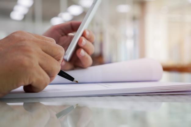 Бизнес-менеджер проверяет и подписывает заявителя, заполняя документы, отчеты, документы, форму заявки компании или регистрируя претензию в офисе. документ отчета и концепция бизнеса занята