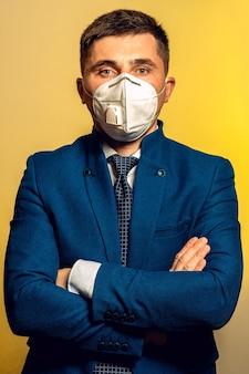Бизнес-менеджер в медицинской маске уверенно стоит со скрещенными руками.