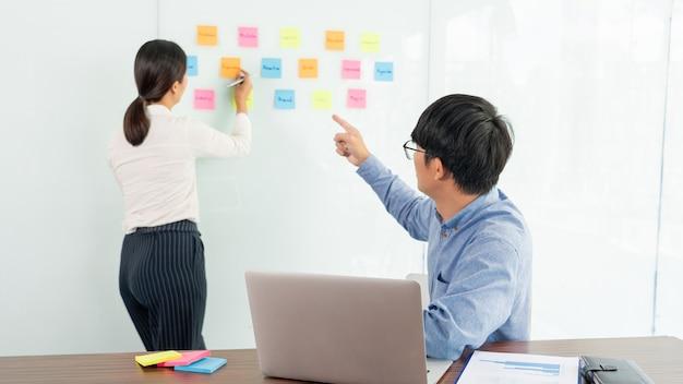 彼女のチームのためのアイデアを示し、ビジネスミーティングのクリエイティブオフィス、計画および管理の概念で成功するためにガラス窓に多くのメモ用紙を貼り付けるビジネスマネージャー。