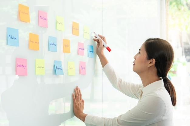 Бизнес-менеджер показывает идею для своей команды и наклеивает много бумаги для заметок на стеклянное окно