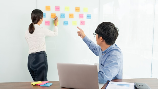 Business manager showing idea for her team and stick many memo paper on glass window to success working in business meeting  creative office, planning and management concept.