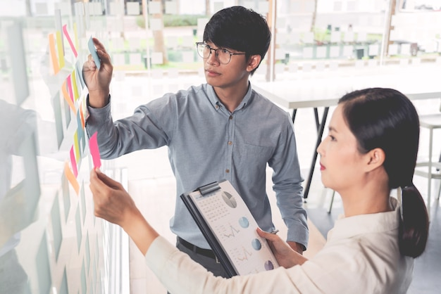 Business manager showing idea for her team and stick many memo paper on glass window