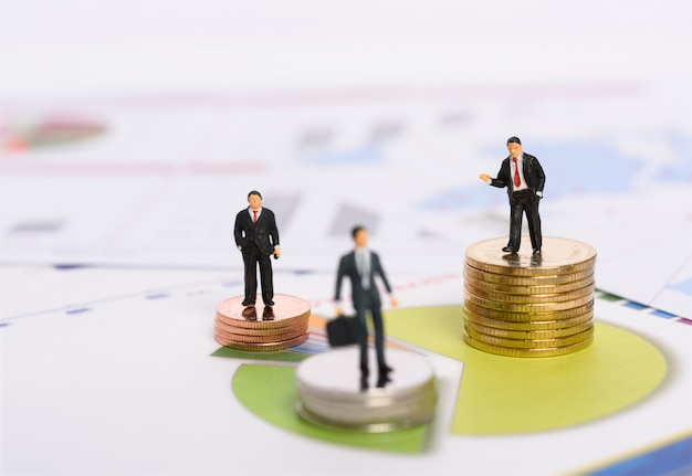 ビジネス市場シェア成長株、ミニチュアビジネス人々はグラフグラフの背景を持つ黄金のコインの上に立つ