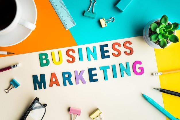 Слово бизнес-маркетинга на столе в офисе с принадлежностями