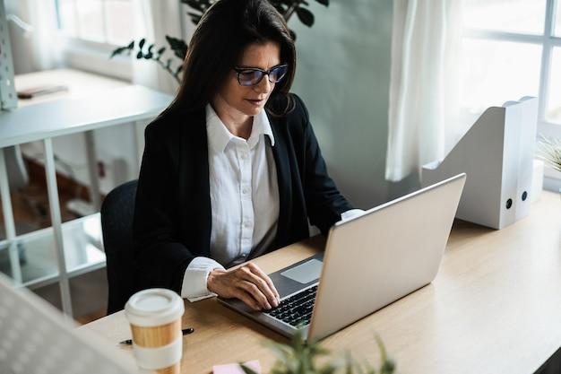 現代のオフィス内でラップトップコンピューターで作業するビジネス成熟した女性-顔に焦点を当てる
