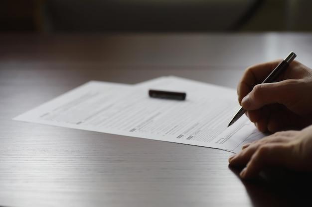 비즈니스 회의입니다. 한 남자가 계약서에 서명합니다. 펜으로 남자 손은 사무실에서 메모를 만듭니다.