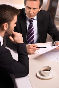 레스토랑에서 비즈니스 회의입니다. 정장 차림의 두 사업가가 무언가를 토론하는 동안 그들 중 한 명이 펜으로 종이를 가리키는 모습