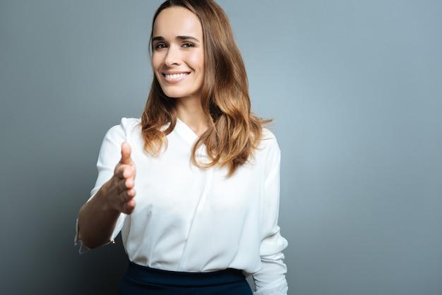 ビジネスミーティング。あなたに挨拶しながら彼女の手を与える笑顔の陽気なポジティブな魅力的な女性