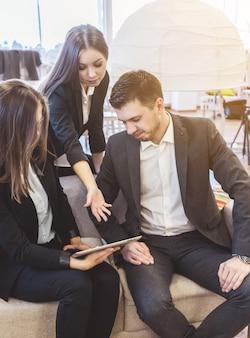 Сотрудники на деловой встрече обсуждают проект в офисе. команда с тремя рабочими в костюмах. люди с планшетным пк