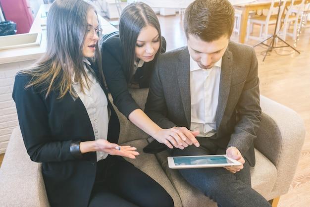 비즈니스 회의 동료는 사무실에서 프로젝트에 대해 논의합니다. 정장을 입은 3명의 작업자와 팀입니다. 태블릿 pc를 사용하는 사람들