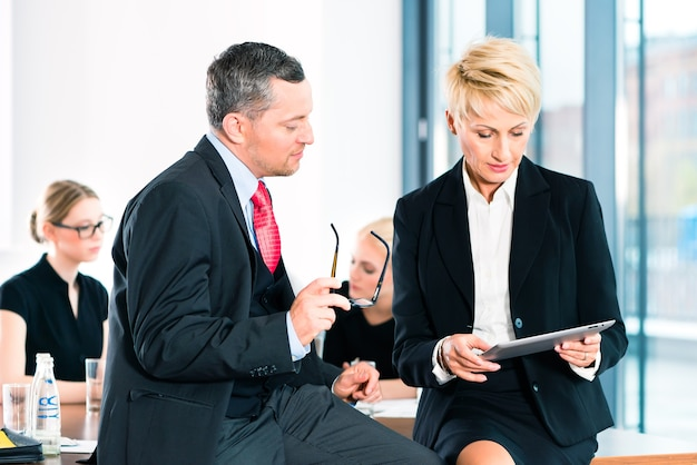 ビジネス-オフィスでの会議、2人の上級管理職がタブレットコンピューターでドキュメントについて話し合っている