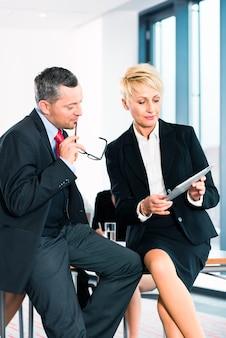 비즈니스-사무실에서 회의, 두 명의 고위 관리자가 태블릿 컴퓨터에서 문서에 대해 논의하고 있습니다.