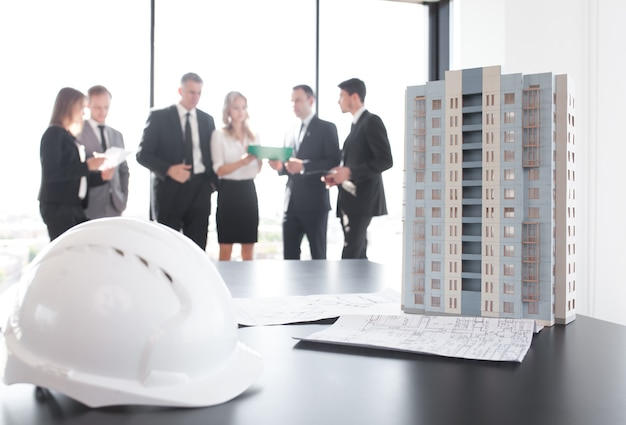 테이블에 현대 다층 주거 건물 집의 모델을보고 건축가와 투자자의 비즈니스 회의