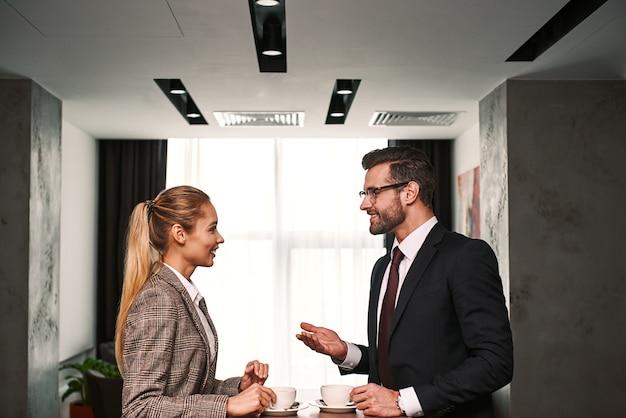 Деловая встреча двух партнеров. бизнесмен и женщина, имеющие бизнес-ланч в холле отеля, пить кофе. женщина смеется над мужскими шутками