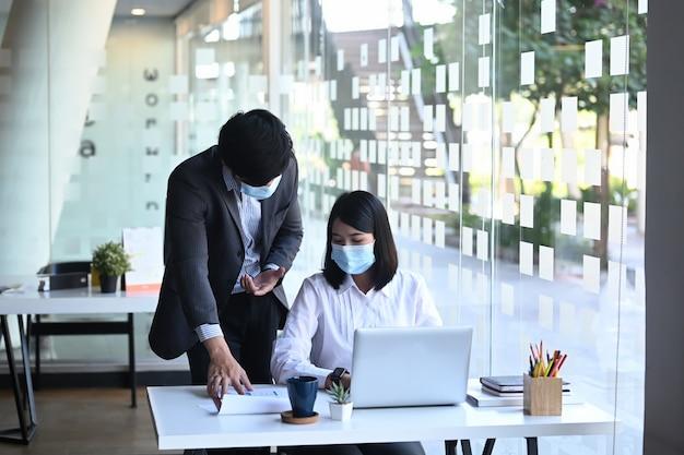 Деловая встреча двух партнеров в защитной маске, работающих вместе и обсуждающих стратегию роста компании в офисе.