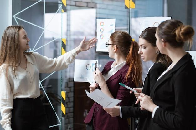 비즈니스 회의. 성공적인 기업 전략 발표. 연간 기업 통계를 가리키는 여성 연사