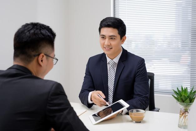 Деловая встреча. два деловых человека сидят друг перед другом в офисе и что-то обсуждают