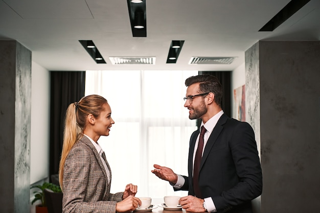 Business meeting of two partners. businessman and woman having business lunch at hotel hall drinking coffee. woman laughting about man's jokes
