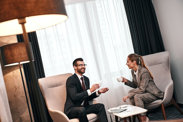 Business meeting of two partners. businessman and woman having business lunch at restaurant drinking coffee. woman laughting about man's jokes