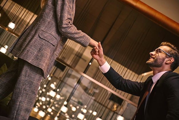 Business meeting of two partners. man and woman having business lunch at restaurant standing shaking hands businessman smiling friendly